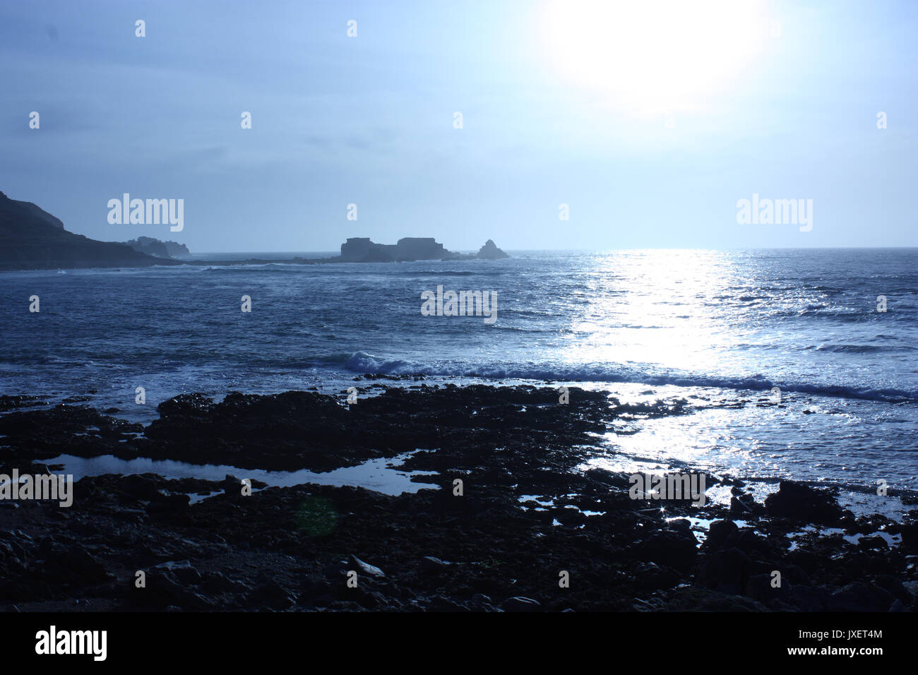 British Channel Islands. Alderney. View of coast and distant Fort Clonque in bright early evening sun. Stock Photo