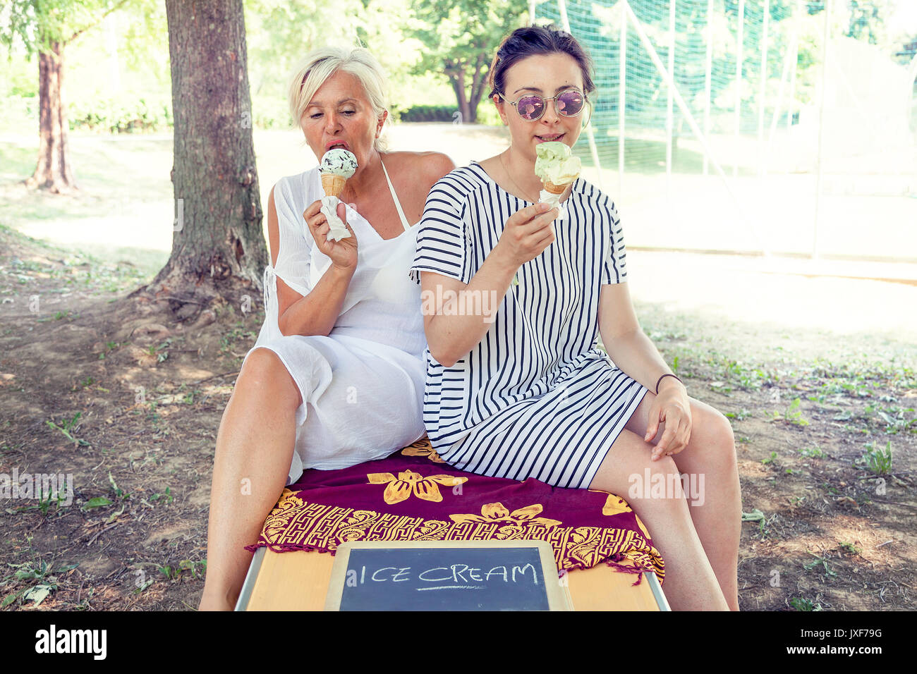 Modern mom and young daughter eating ice cream sitting on a deckchair in a water park on summertime. Concept of beautiful people having fun in summert - Stock Image