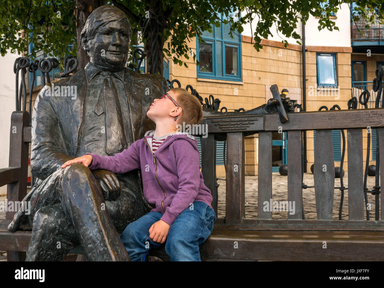Close up young boy with glasses admiring bronze commemorative sculpture of Sandy Irvine Robertson, local wine merchant on a bench in Leith, Edinburgh - Stock Image