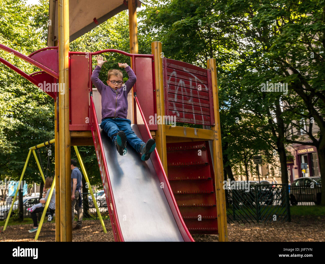 Young disabled boy with glasses and carbon fibre leg brace being brave going down slide in adventure playground, Leith, Edinburgh, Scotland, UK - Stock Image