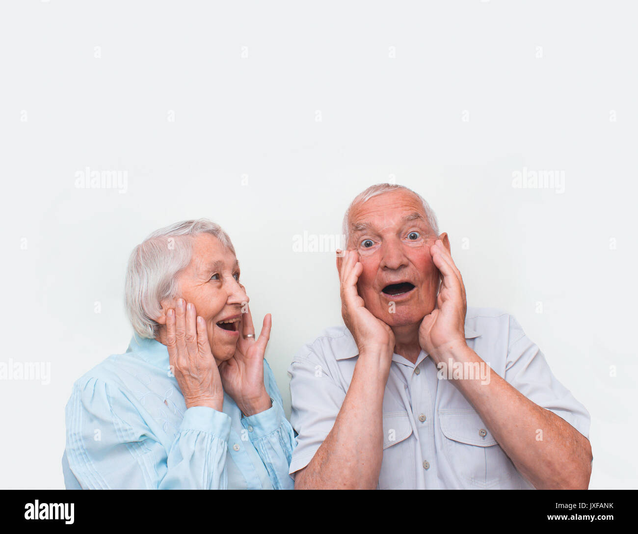 The elderly couple surprised by raising both hands - Stock Image