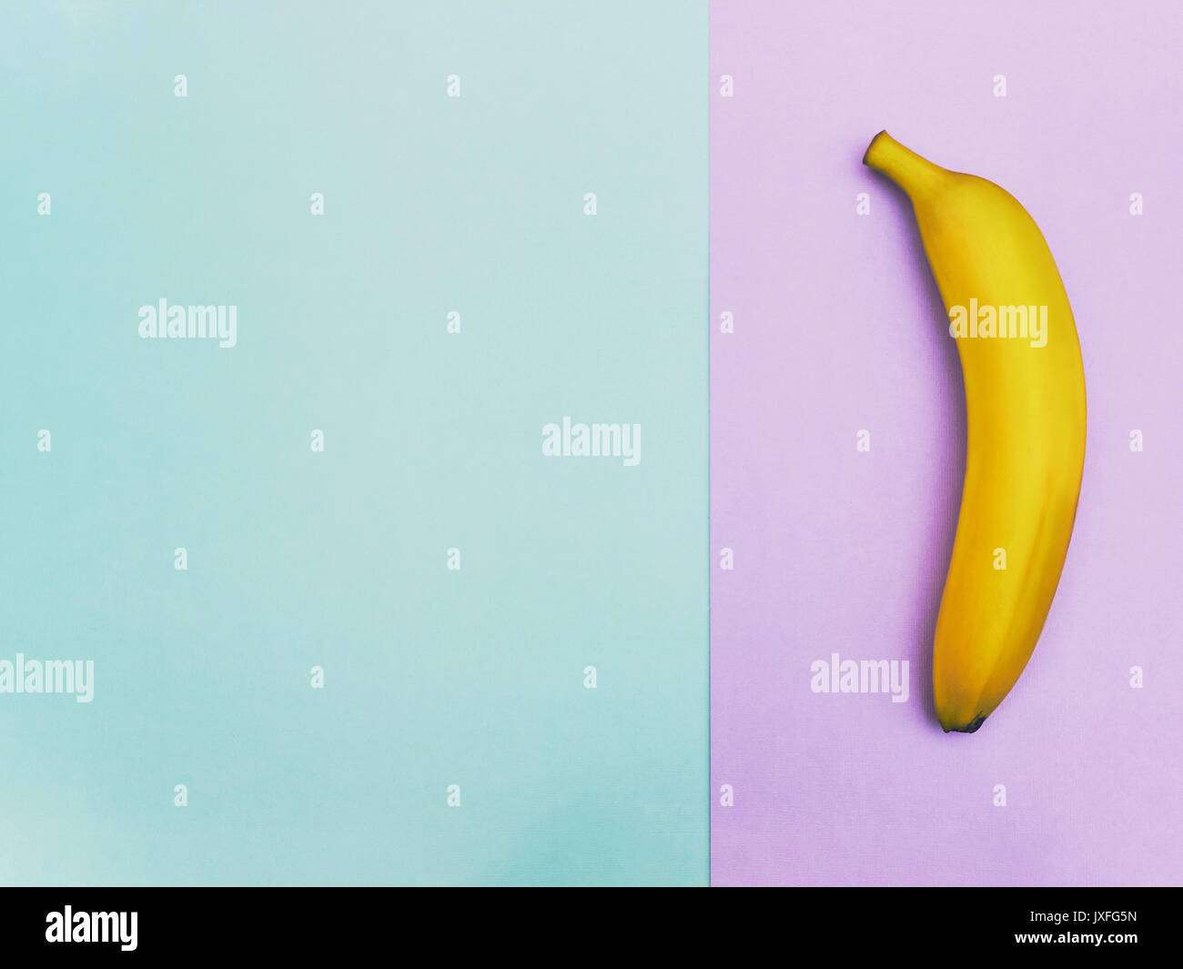 Fruit in flat lay Ripe yellow banana is lying on two-tone background Top view Trendy colorful flat lay photo of banana with space for text - Stock Image