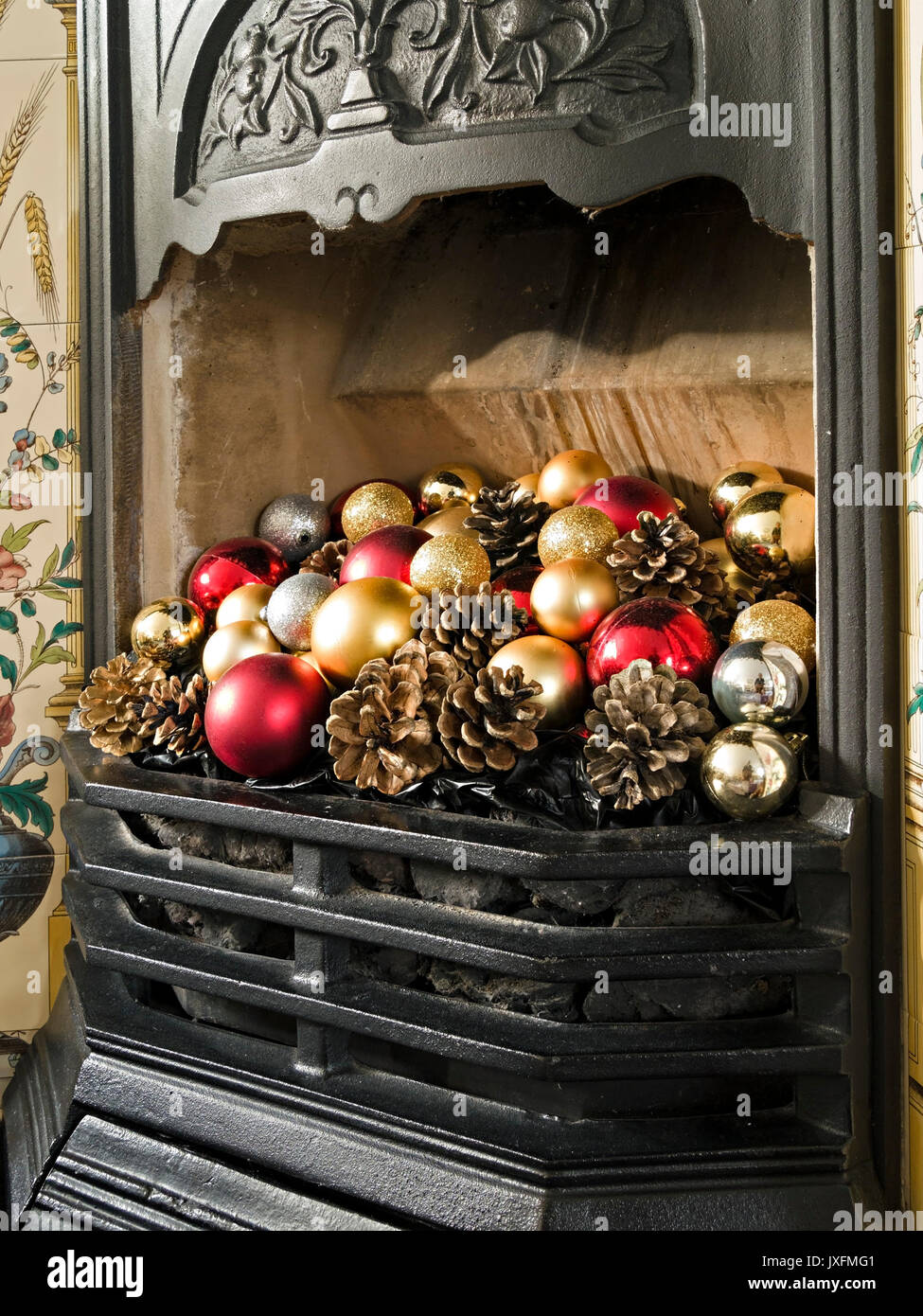 Pretty victorian style cast iron fireplace and grate decorated with colourful Christmas baubles and fir cones, England, UK - Stock Image