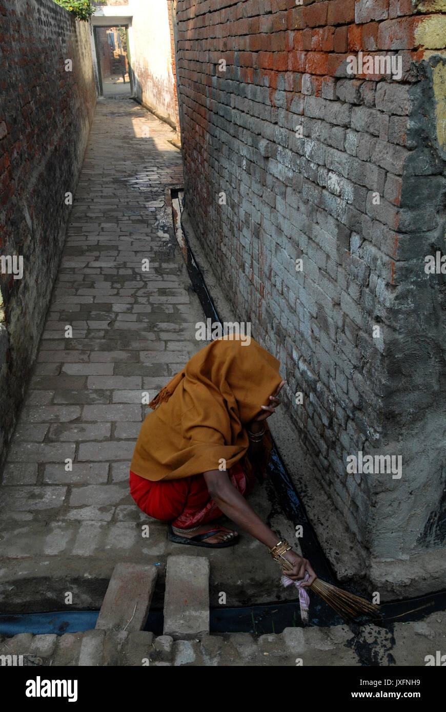 India UP Meerut , dalit woman clean toilets and sewage canal for higher caste households in village Kurali  / INDIEN U.P. Meerut, Kastensystem, Dalit Frau reinigt Toiletten und Abwasserkanal fuer hoeherkastige Haushalte  im Dorf Kurali - - Stock Image