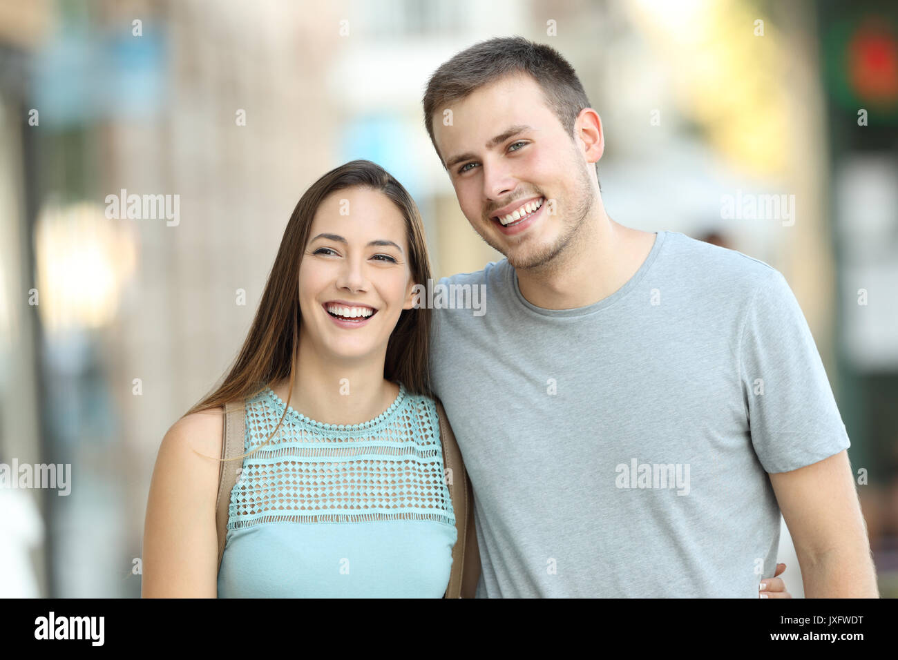 Front view portrait of a happy couple walking together on the street - Stock Image