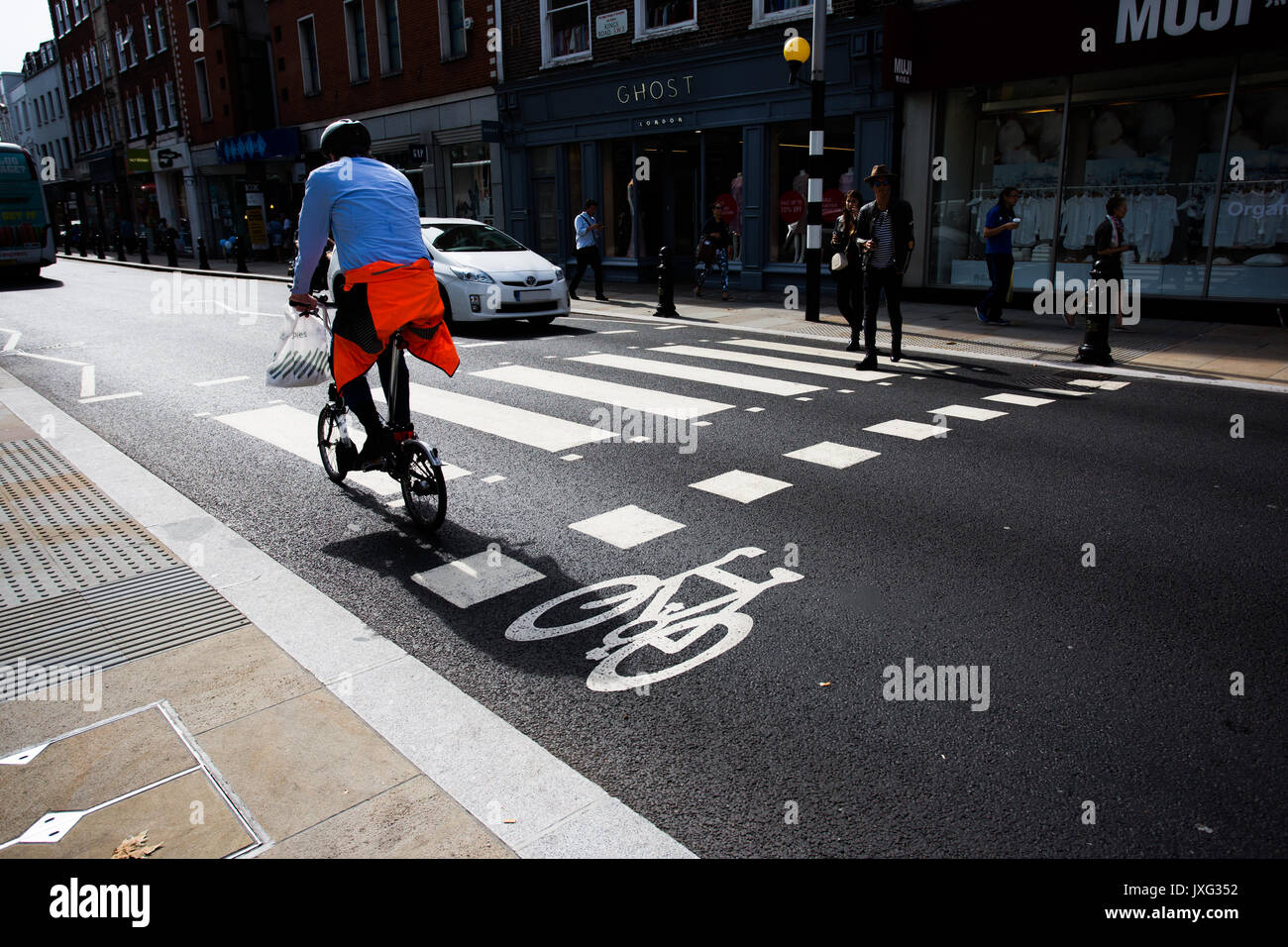 A London worker cycling over zebra crossing whilst car waits for pedestrian on Kings Road, Sloane Square, London. Stock Photo