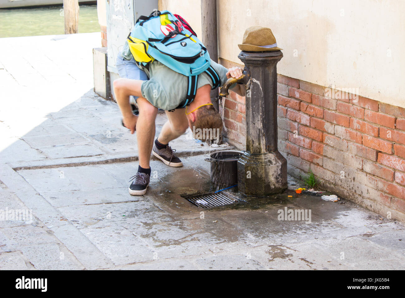 A man cooling himself in a hot summer day in Venice, Italy - Stock Image