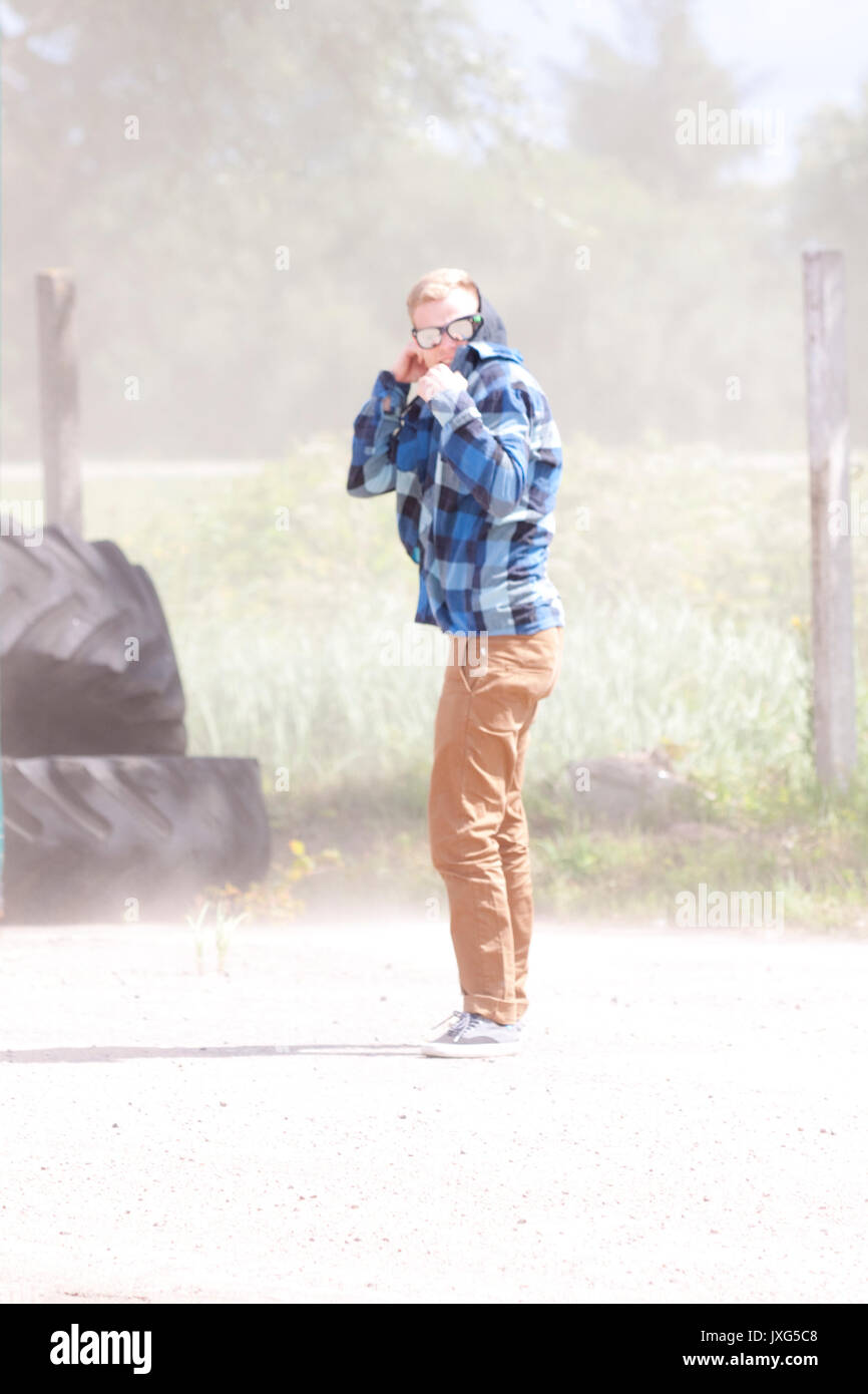A man covering himself from a nasty dust squall - Stock Image