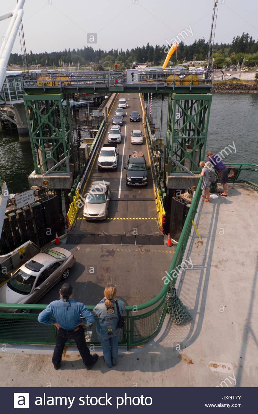 People watching automobiles loading onto a Washington State ferry docked at Kingston, Kitsap County, Washington, USA - Stock Image