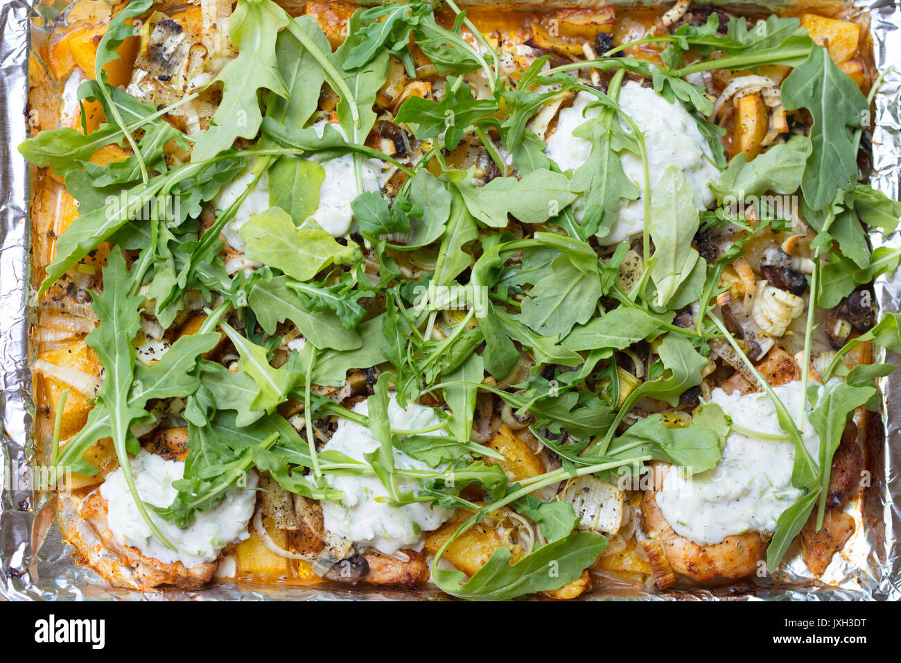 Oven roasted chicken and yukon gold potatoes, leeks, arugula and tzatziki sauce on a baking sheet lined with aluminum foil - Stock Image