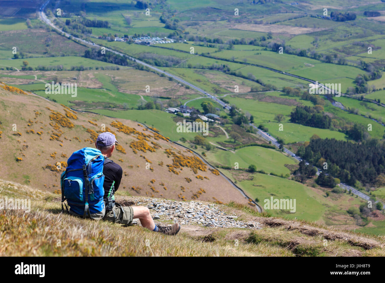 Hillwalker relaxing on the Mountainside admiring the views - Stock Image