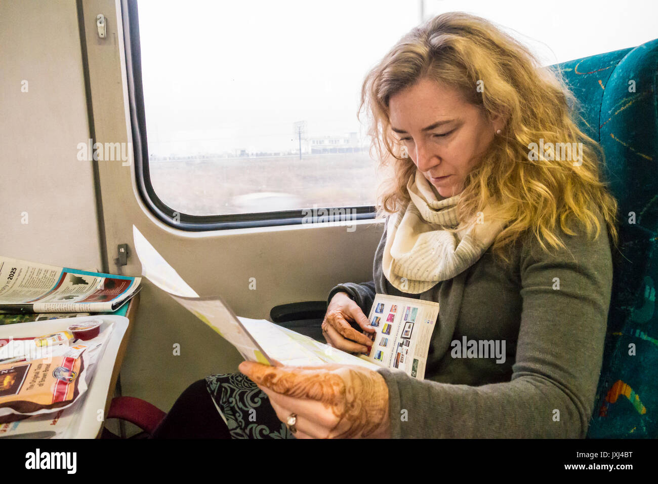 A woman on a train between Dehli and Agra India studying travel information and maps. - Stock Image
