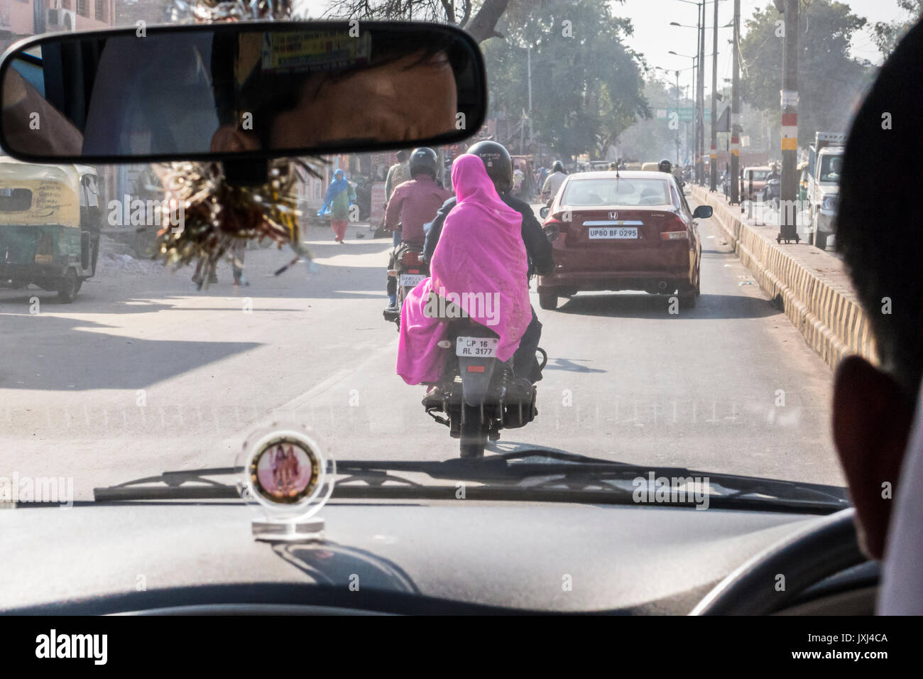 Looking out the front windshield of a car while driving in India seeing a woman in a bright pink sari while seated on the back of a motorcycle. Agra,  - Stock Image