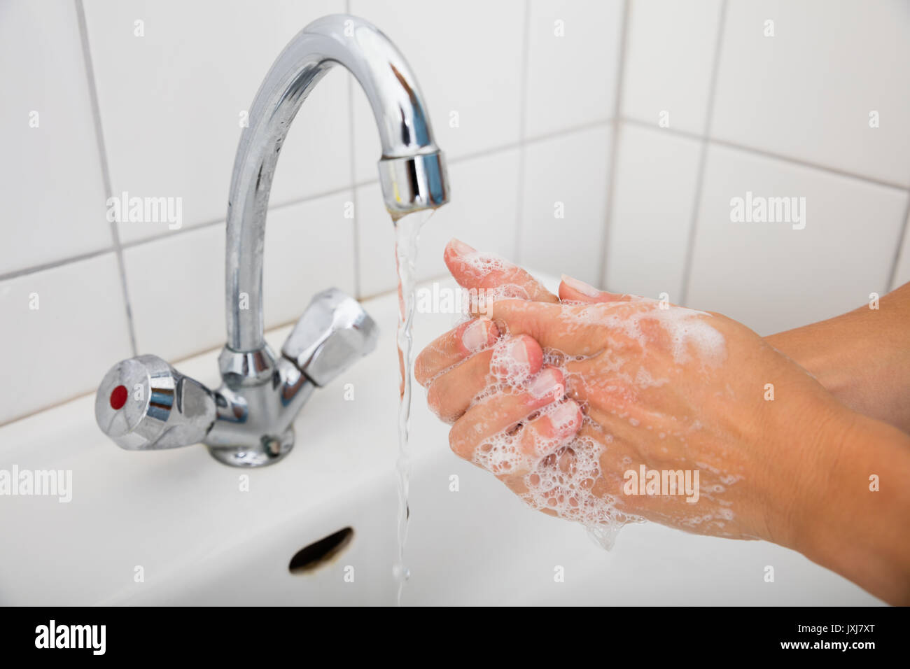 Close-up Of Woman Applying Soap While Washing Hands In Basin With Open Tap - Stock Image