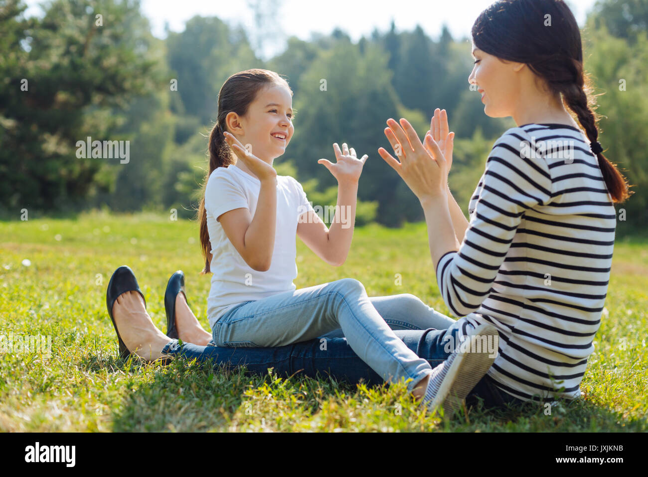 Happy daughter playing pat-a-cake with her mother outdoors - Stock Image