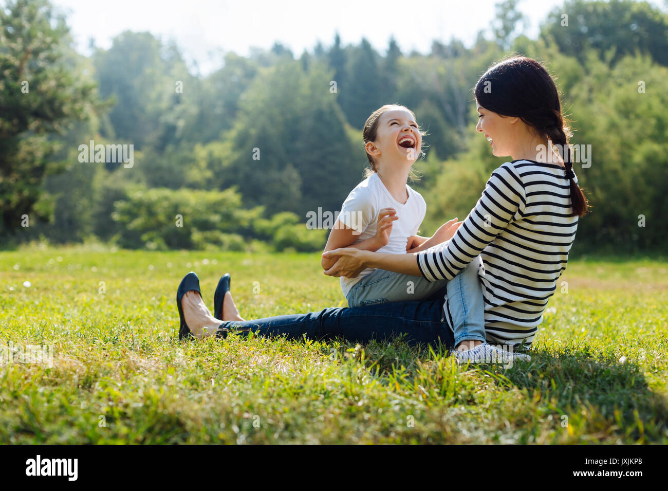 Cheerful daughter and mother laughing together outdoors - Stock Image