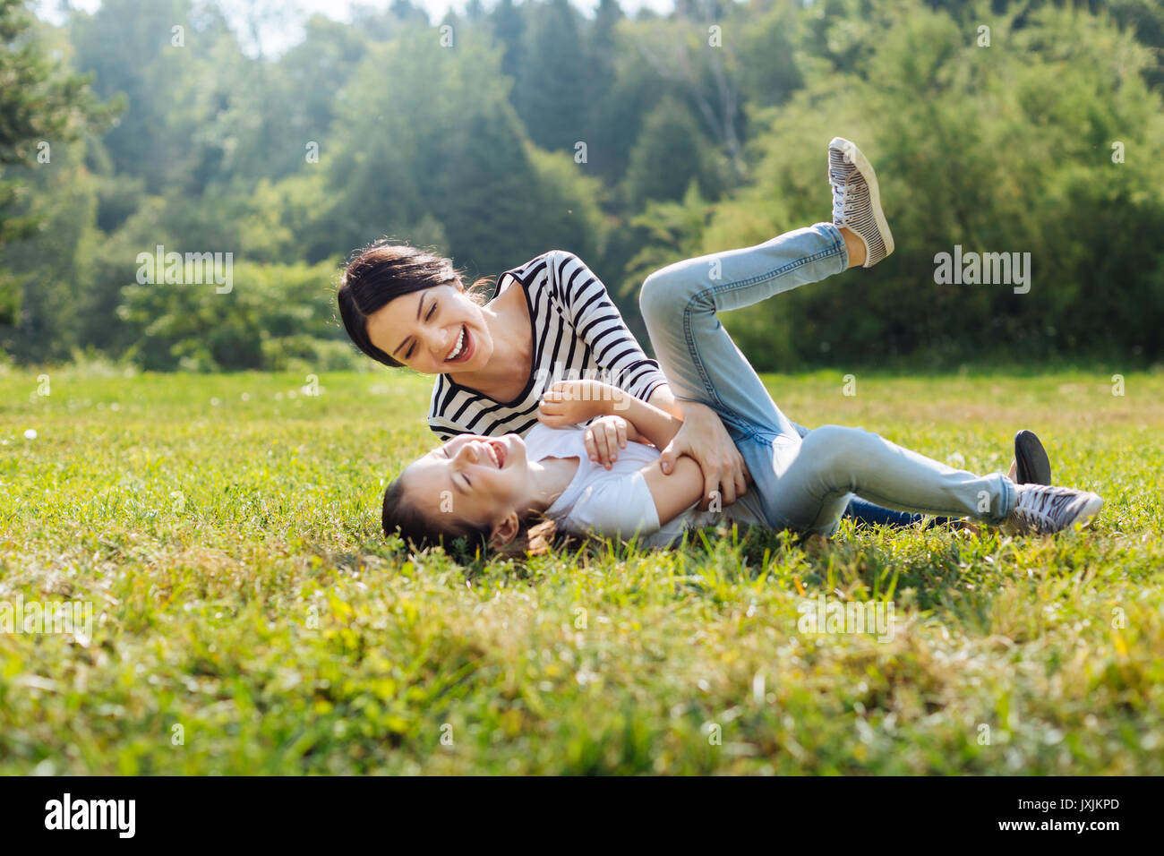 Cheerful mother and daughter goofing around on grass in park - Stock Image