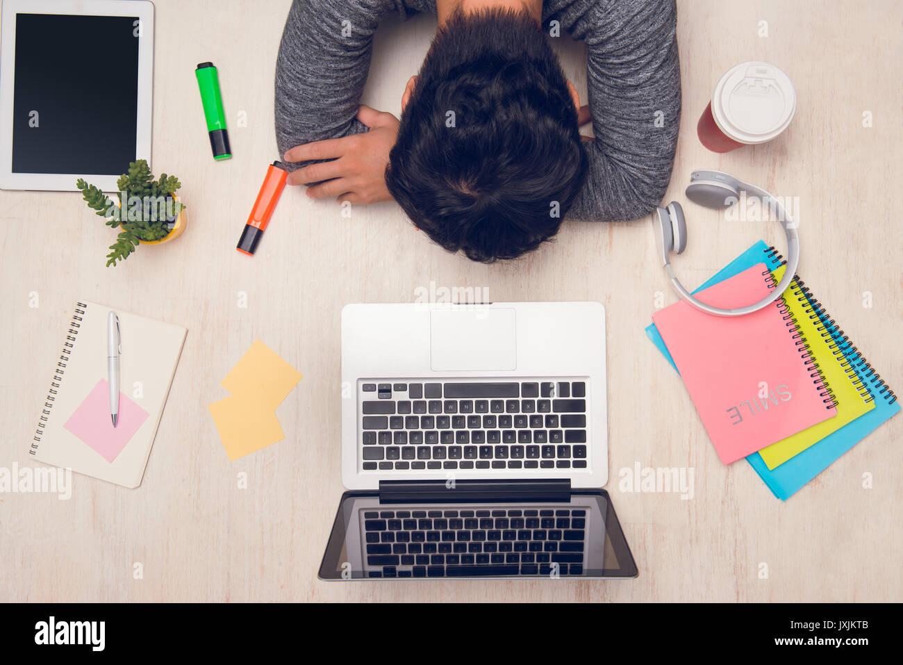 https://c8.alamy.com/comp/JXJKTB/student-guy-sleeping-on-desk-with-books-around-top-view-JXJKTB.jpg