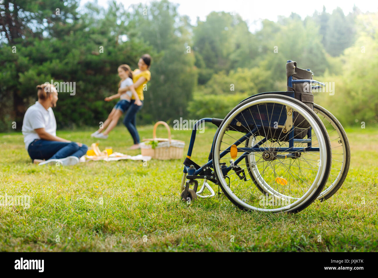 Disabled man watching his wife spin daughter - Stock Image