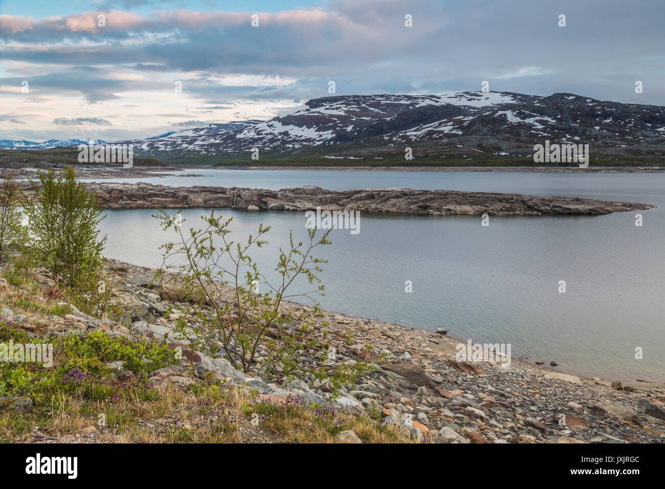 Sunset over Laponia, Stora sjöfallets national park with nice warm colors on the sky reflecting in the water, little snow on the mountains, Stora sjöf - Stock Image