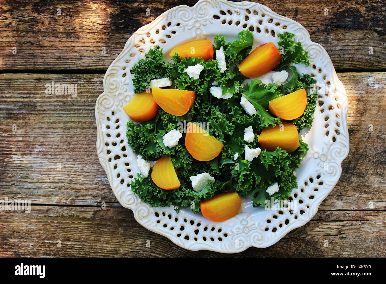 Healthy Beet Salad with fresh kale lettuce, nuts, feta cheese on wooden background - Stock Image