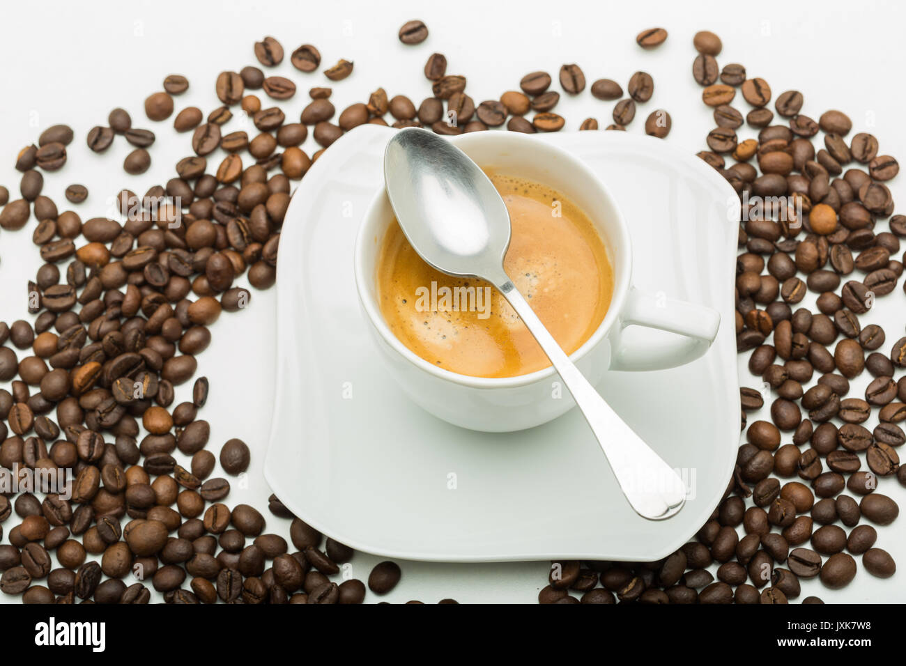 A white cup of coffee and a white saucer seen from the top with coffee beans. - Stock Image