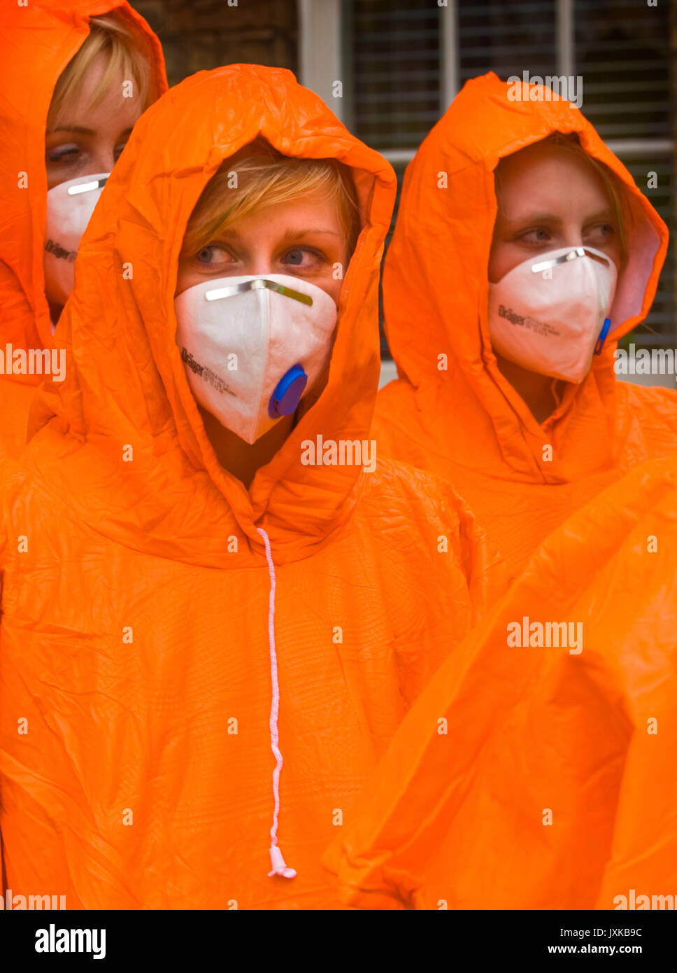 Medical students taking part in a simulated chemical contamination emergency wear brightly coloured coveralls and leave their own clothing in the desi - Stock Image
