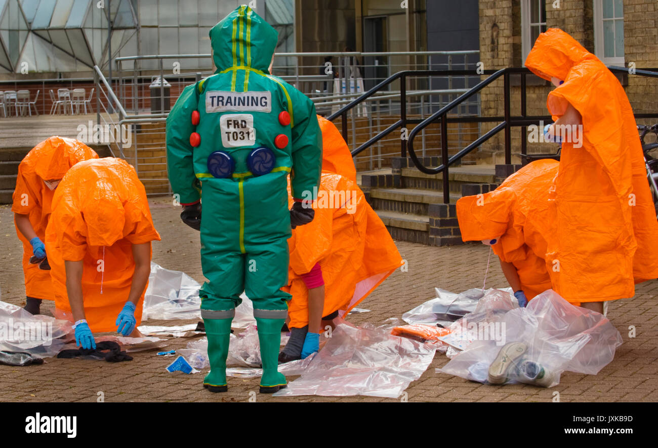 Emergency response paramedic in PRPS (Powered Respirator Protective Suit) clothing supervises students changing into brightly coloured coveralls after - Stock Image