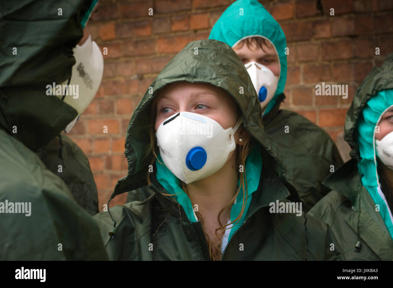 Decontaminated subjects in simulated chemical contamination incident wearing hood & face-mask. - Stock Image