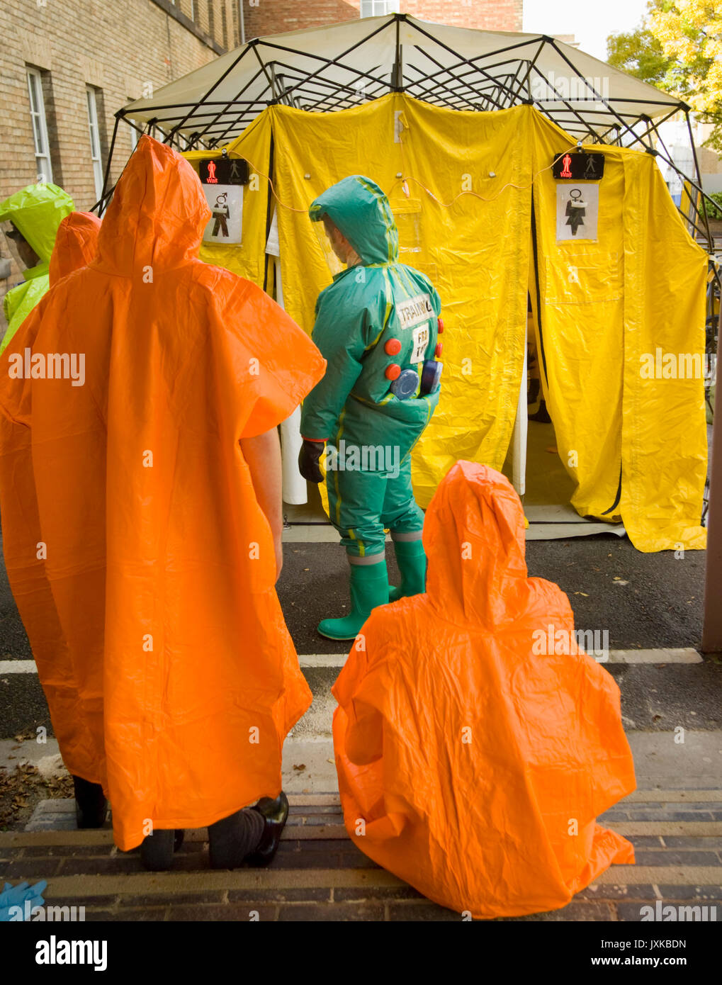 'Contaminated' subjects waiting for de-contamination shower under the supwervision of a Fie & Rescue Service co-ordinator wearing  PRPS (Powered Respi - Stock Image