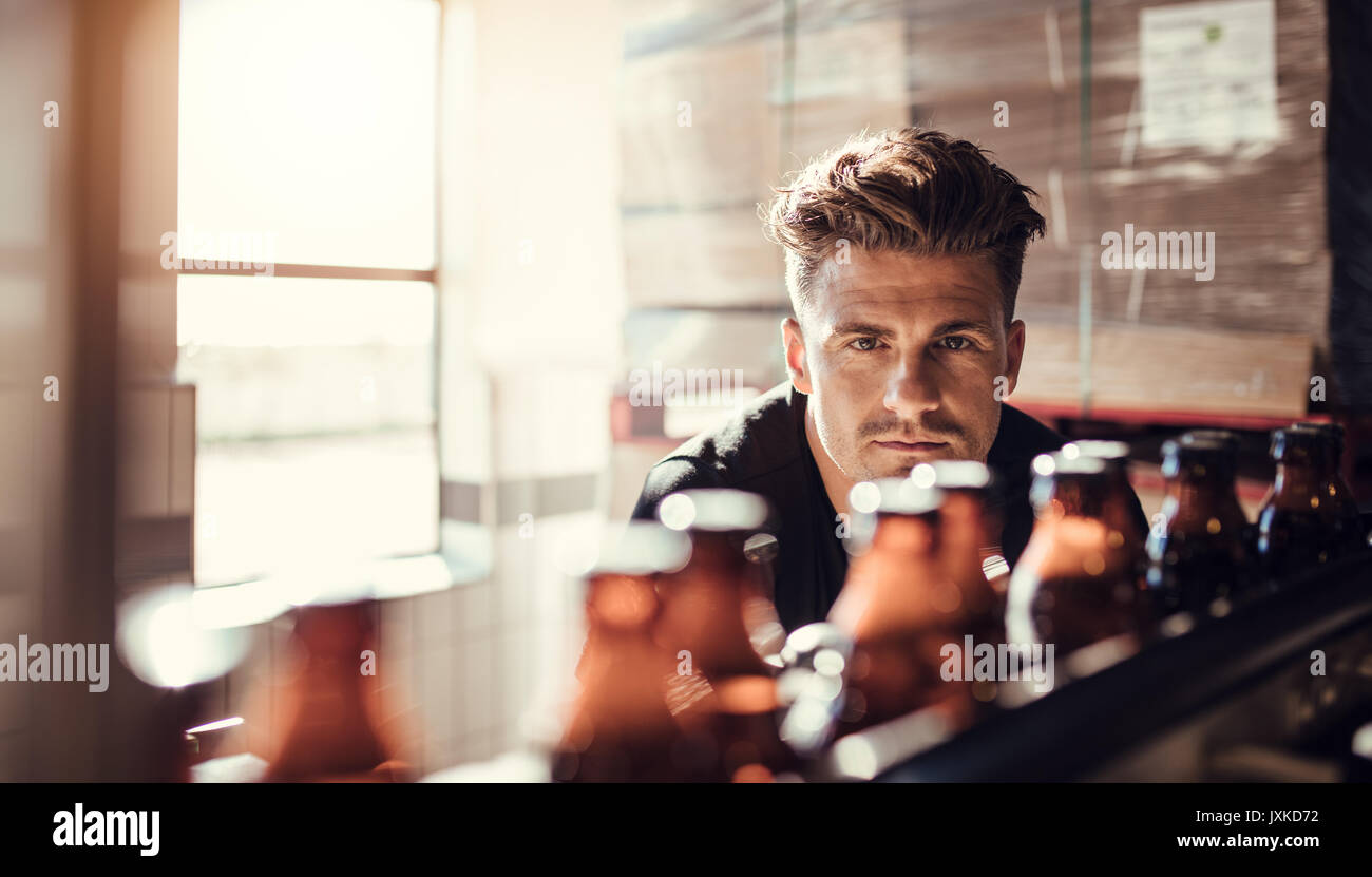 Male brewer looking at conveyor with beer bottles moving. Young man supervising the process of beer bottling at - Stock Image
