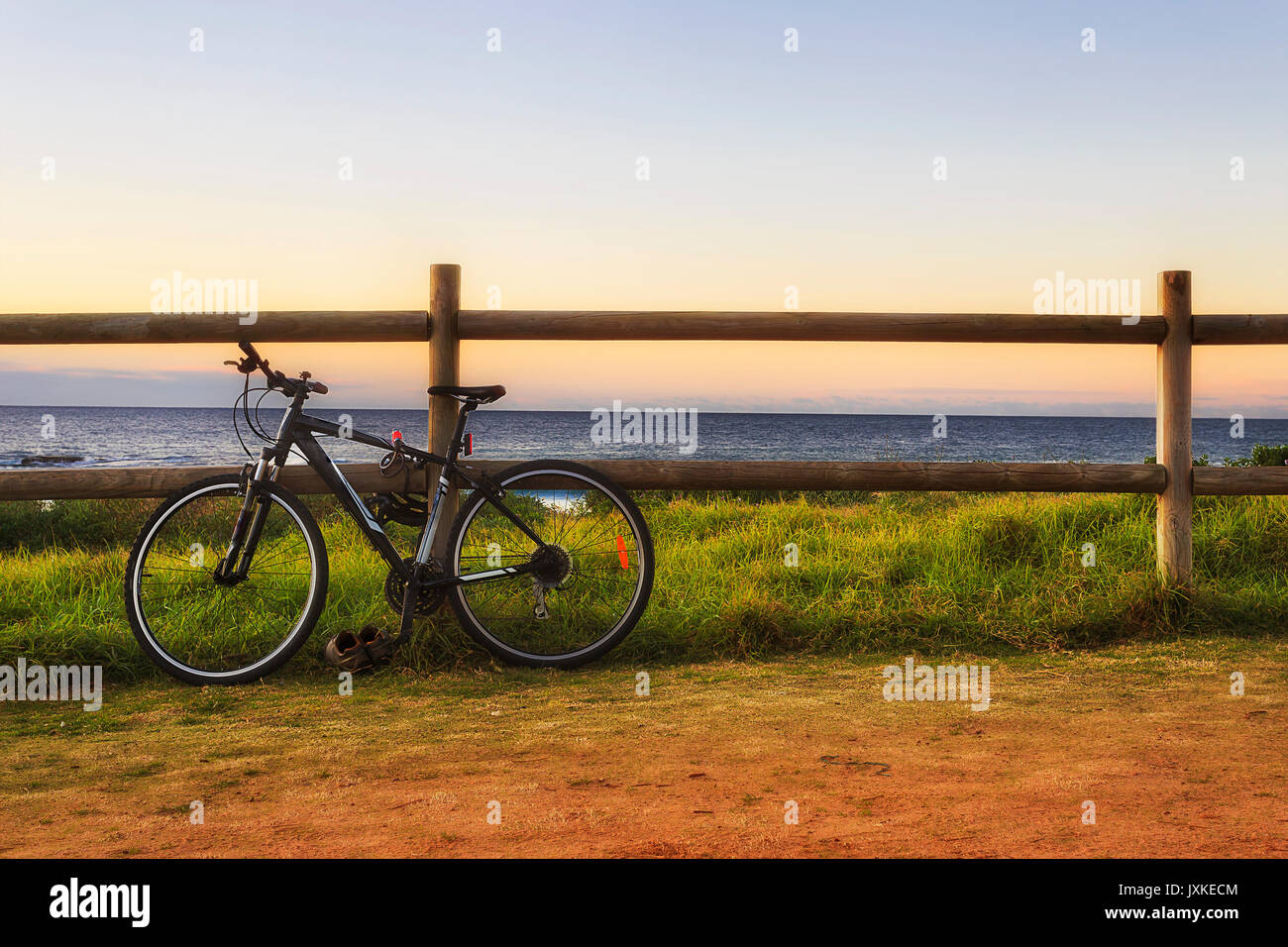Black modern sport bicycle secured at the wooden pole of fence at the empty beach at sunrise. - Stock Image