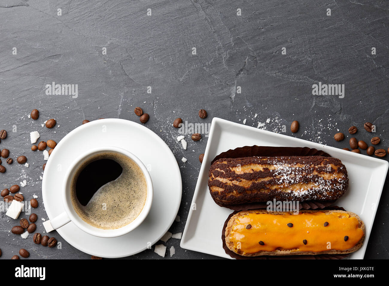 Cup of coffee with french eclairs on dark stone background - Stock Image