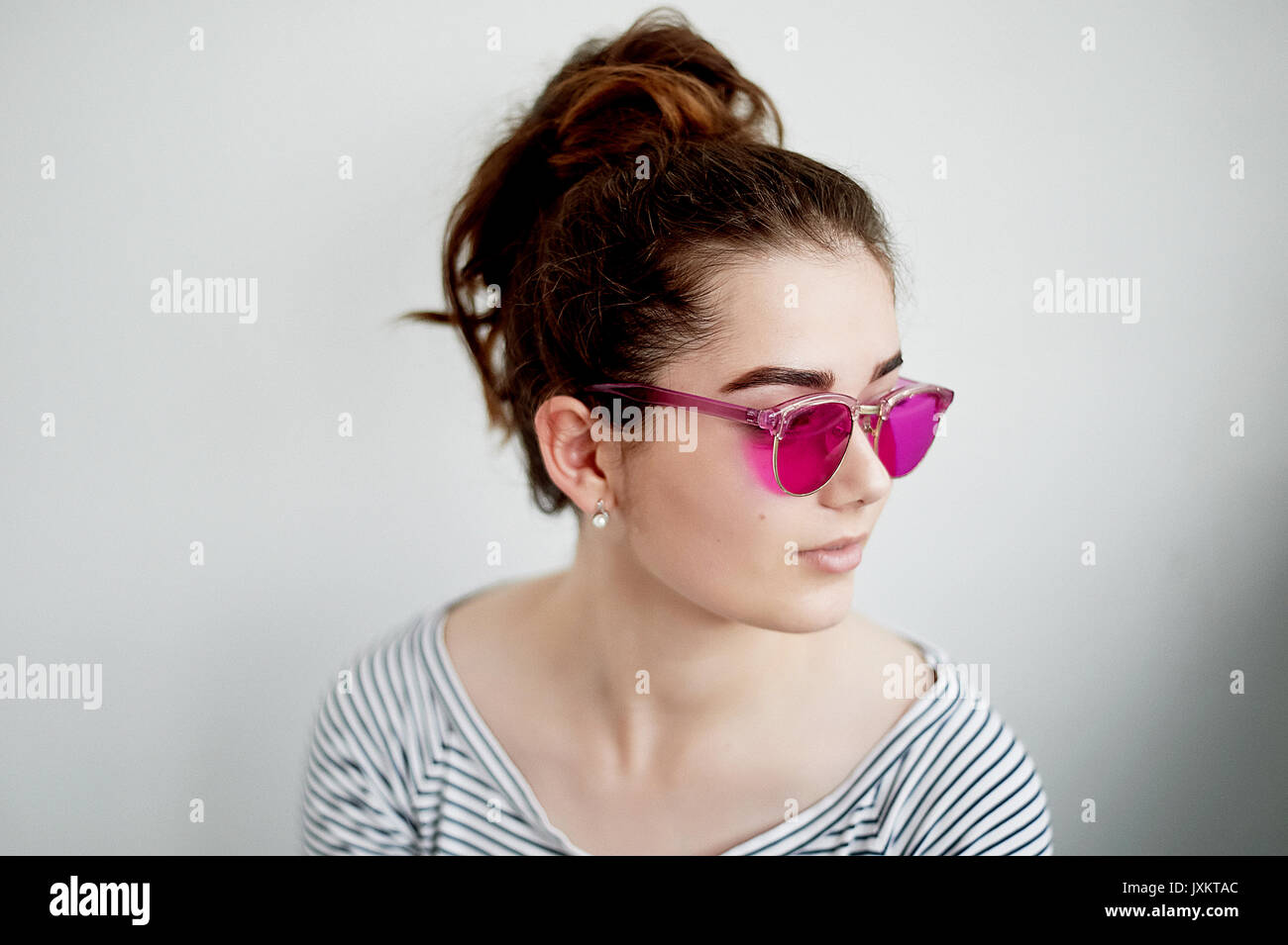 The girl smiles happily in the pink glasses.A naive view of the world in the transition to adulthood - Stock Image