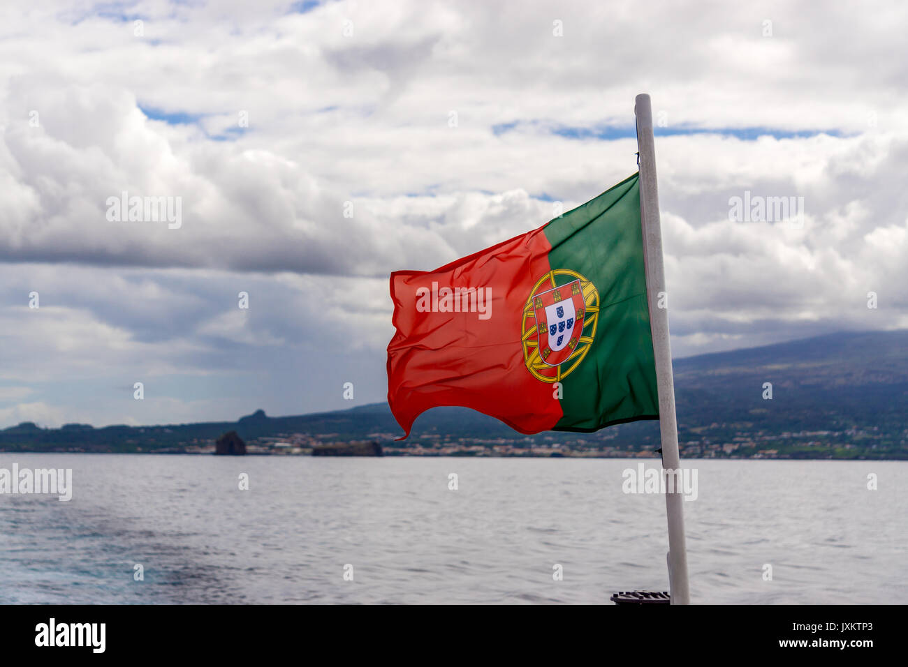 Portuguese flag fluttering in the wind, with the island of Pico in the background - Stock Image