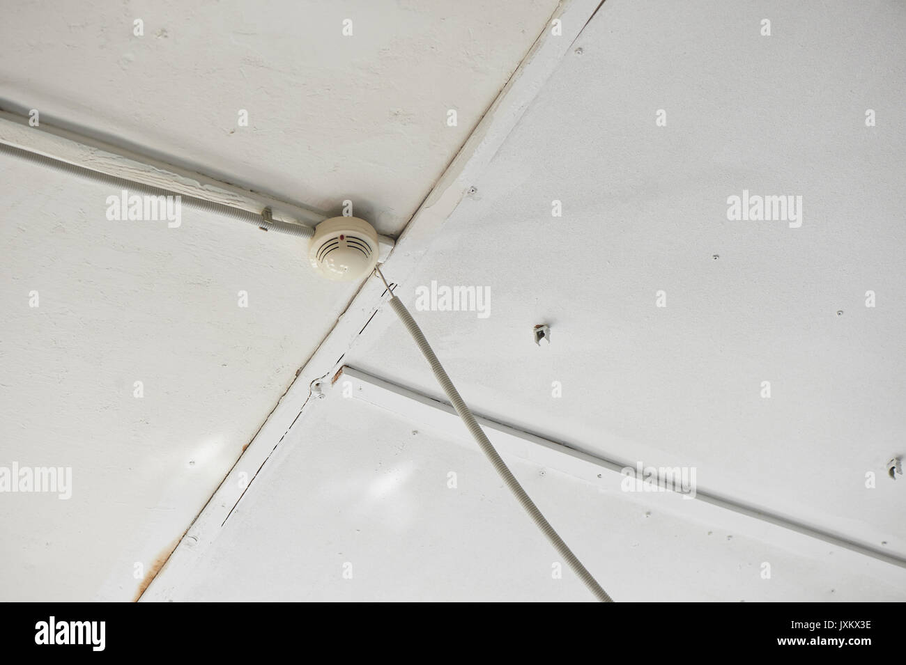 Smoke detector of fire alarm on white wooden ceiling. Stock Photo