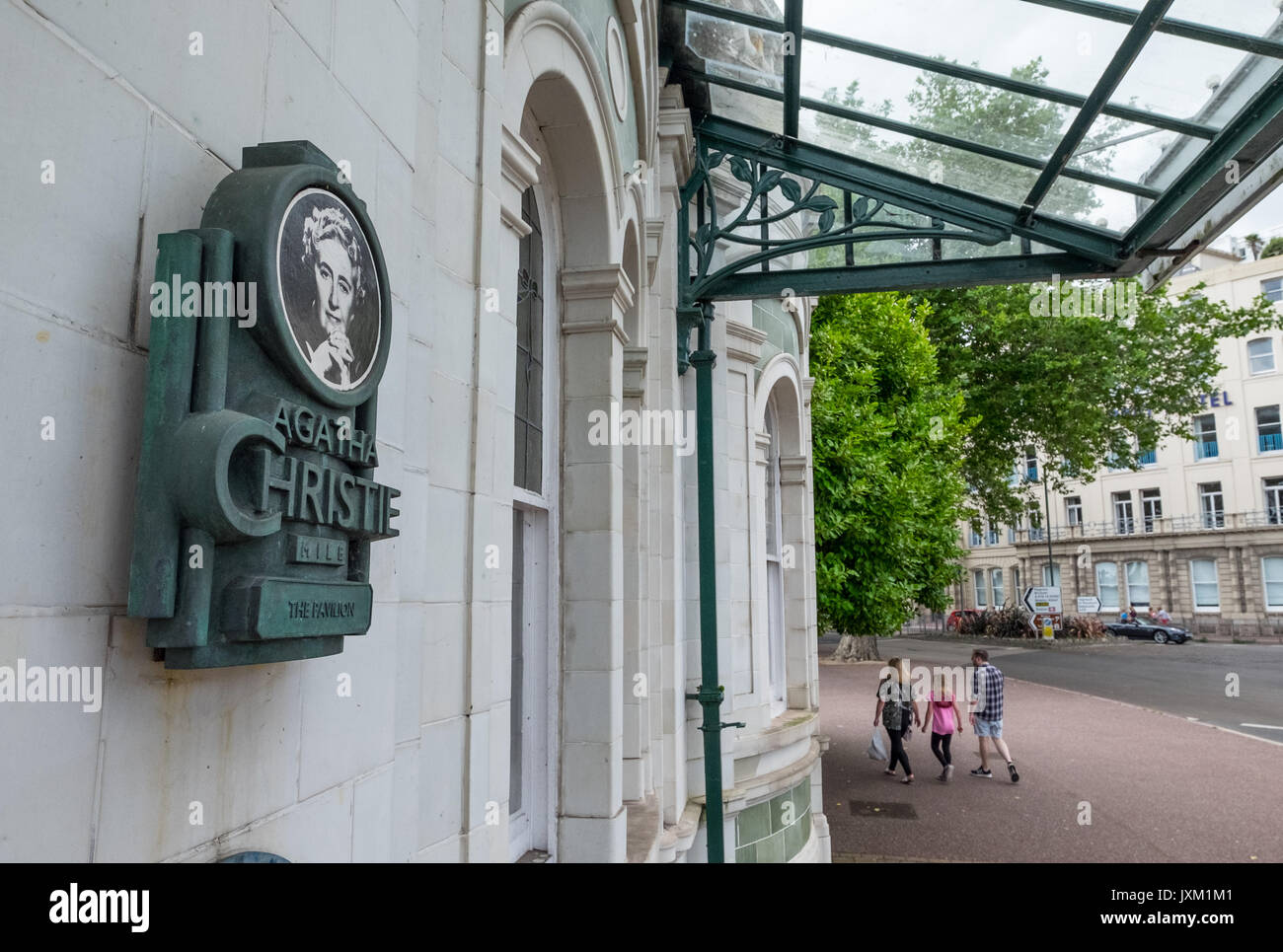 Tourist pass an Agatha Christie Mile sign on the Pavilion in Torquay, Devon, UK - Stock Image