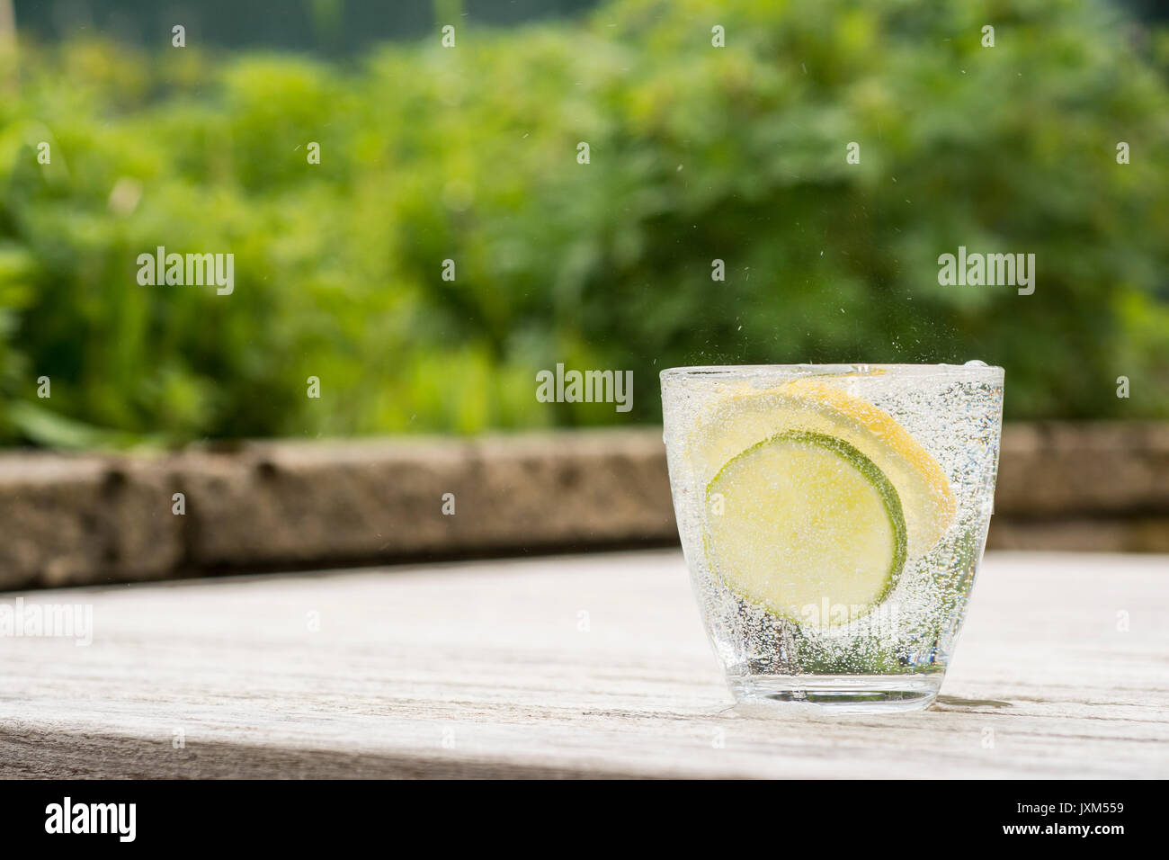 Glass of gin and tonic or vodka and tonic or fizzy water on a wooden table. Refreshing - Stock Image