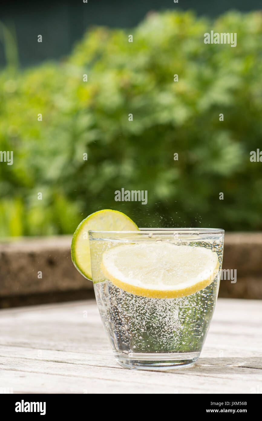 Glass of gin and tonic or vodka and tonic or fizzy water on a wooden table. Refreshing Stock Photo