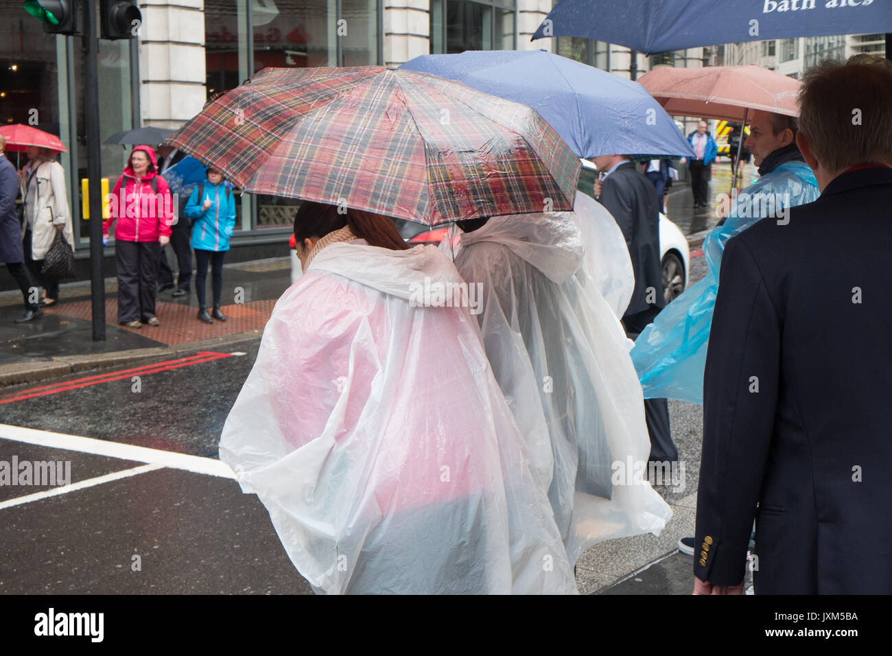 Tourists,wearing,ponchos,Torrential,all day,Rainy,rain,day,August,summer,umbrella,umbrellas,in,The City,City,business,district,London,England,U.K.,UK, - Stock Image