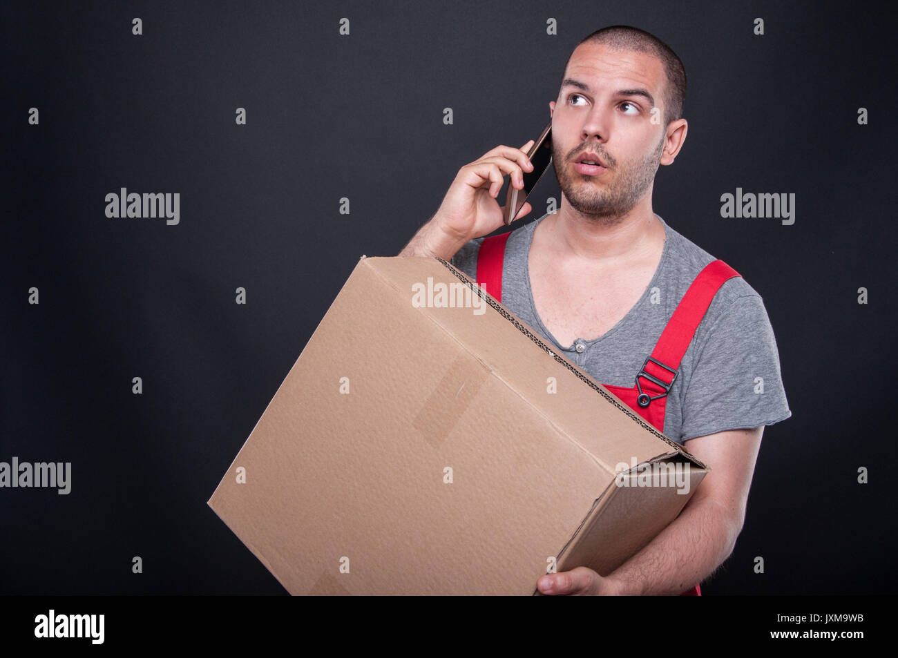 Mover man holding box talking on mobile phone on black background with copy space text - Stock Image