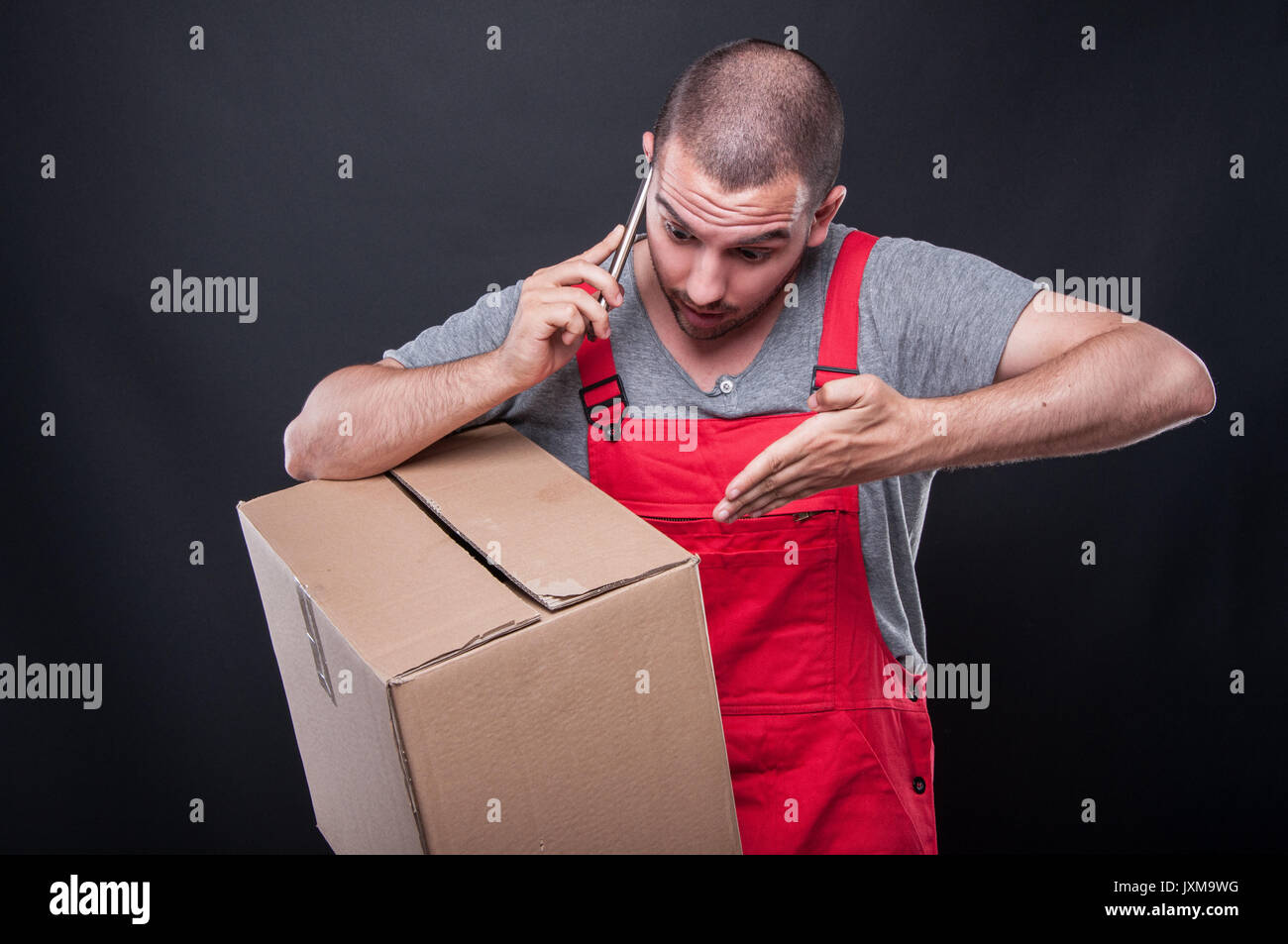 Mover man holding box giving explanation o phone on black background with copy space text - Stock Image