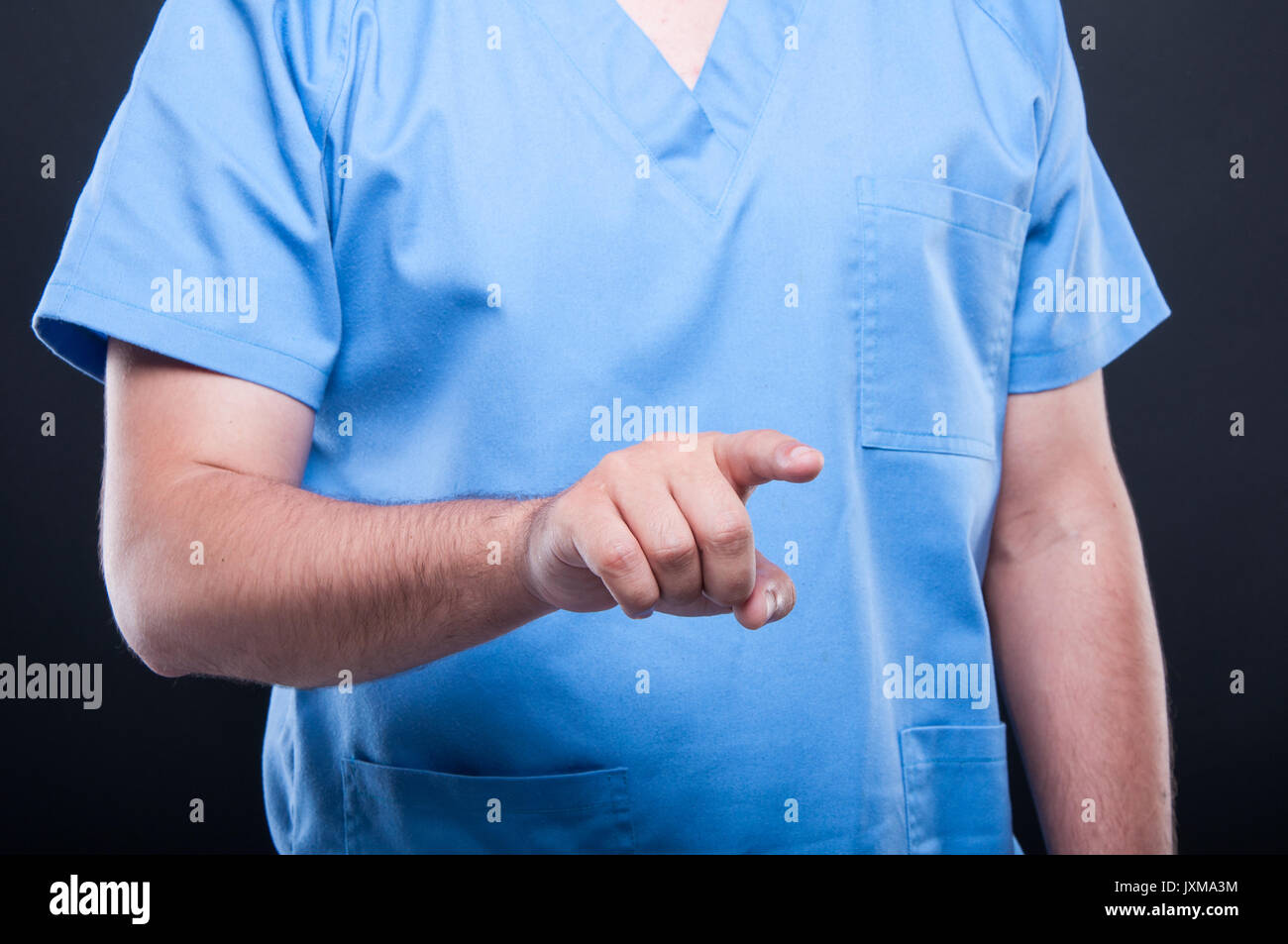a537ea44d57 Close-up of medical nurse wearing scrubs using touchscreen on black  background - Stock Image