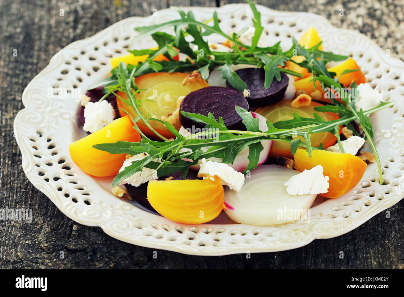 Healthy Beet Salad with red, white, golden beets, arugula, nuts, feta cheese on wooden background - Stock Image