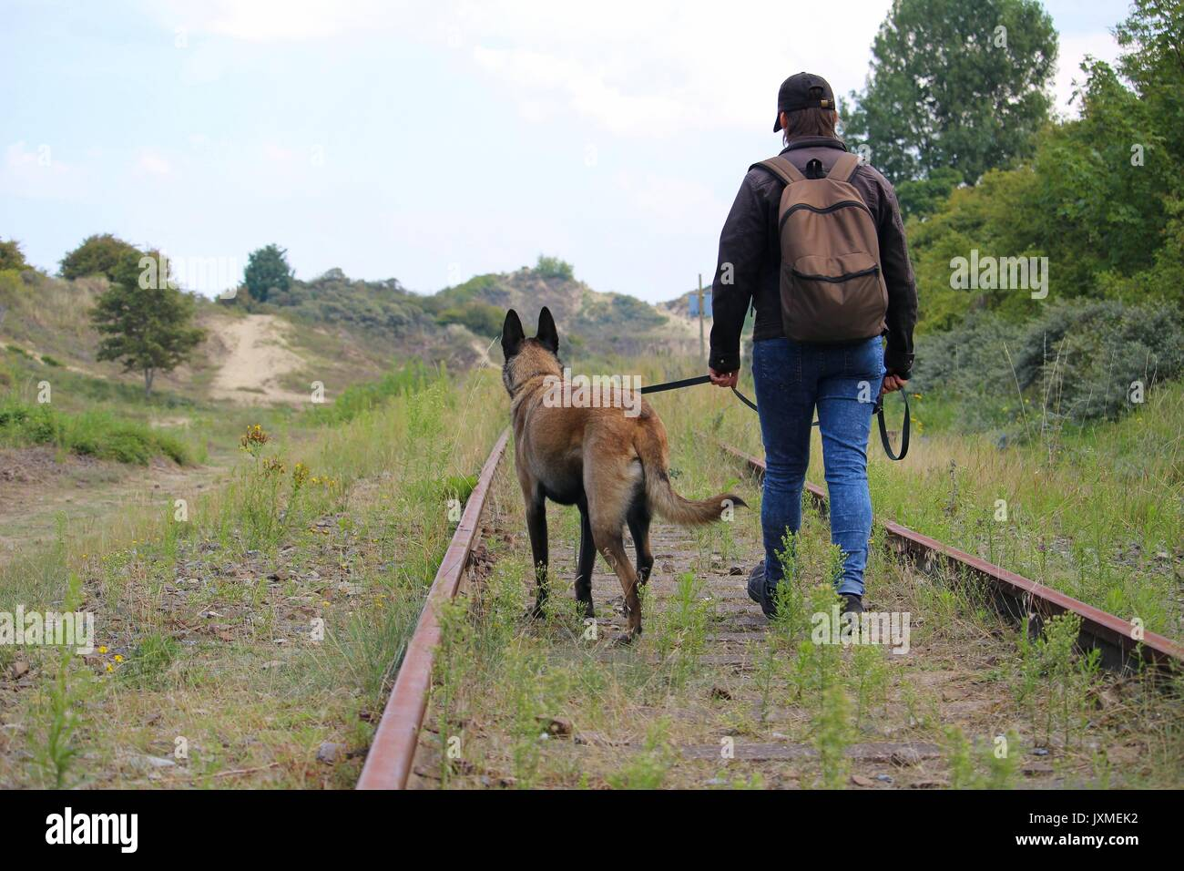 A master and his dog on a walk along the rails near the dunes - Stock Image