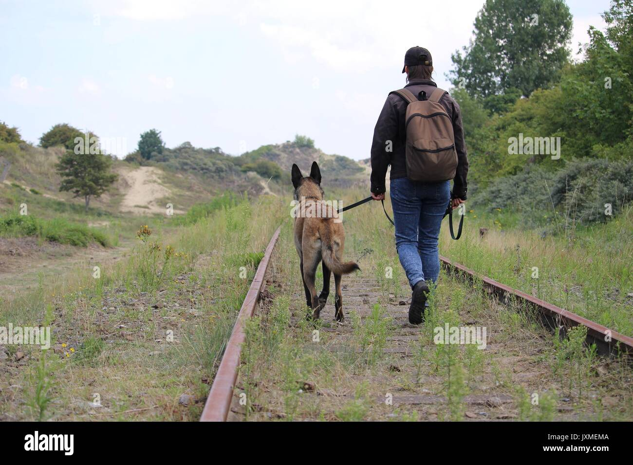 A master and his Malinois Belgian shepherd who walks along the rails - Stock Image