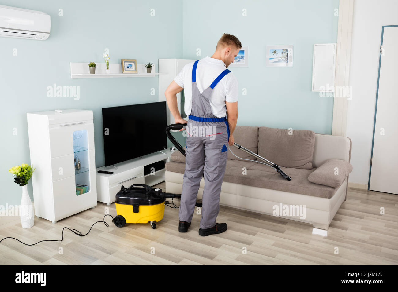 Rear View Of Young Male Worker Cleaning Sofa With Vacuum Cleaner - Stock Image