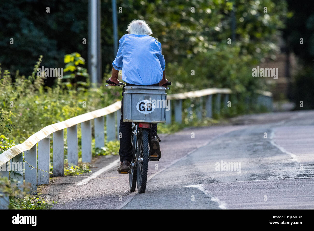 Male riding a bicycle on a country lane with G.B. sticker. - Stock Image