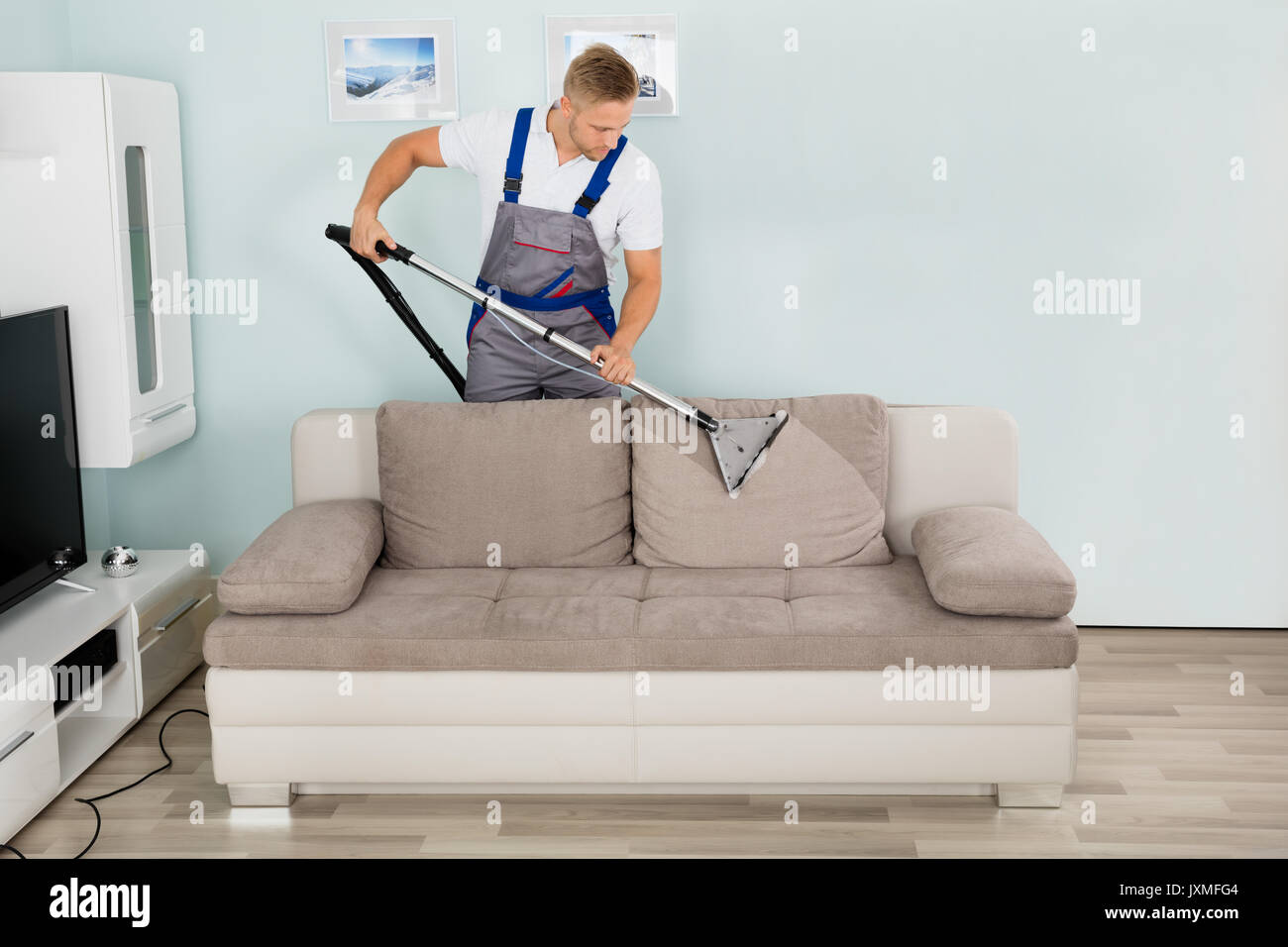 Young Male Worker Cleaning Sofa With Vacuum Cleaner - Stock Image