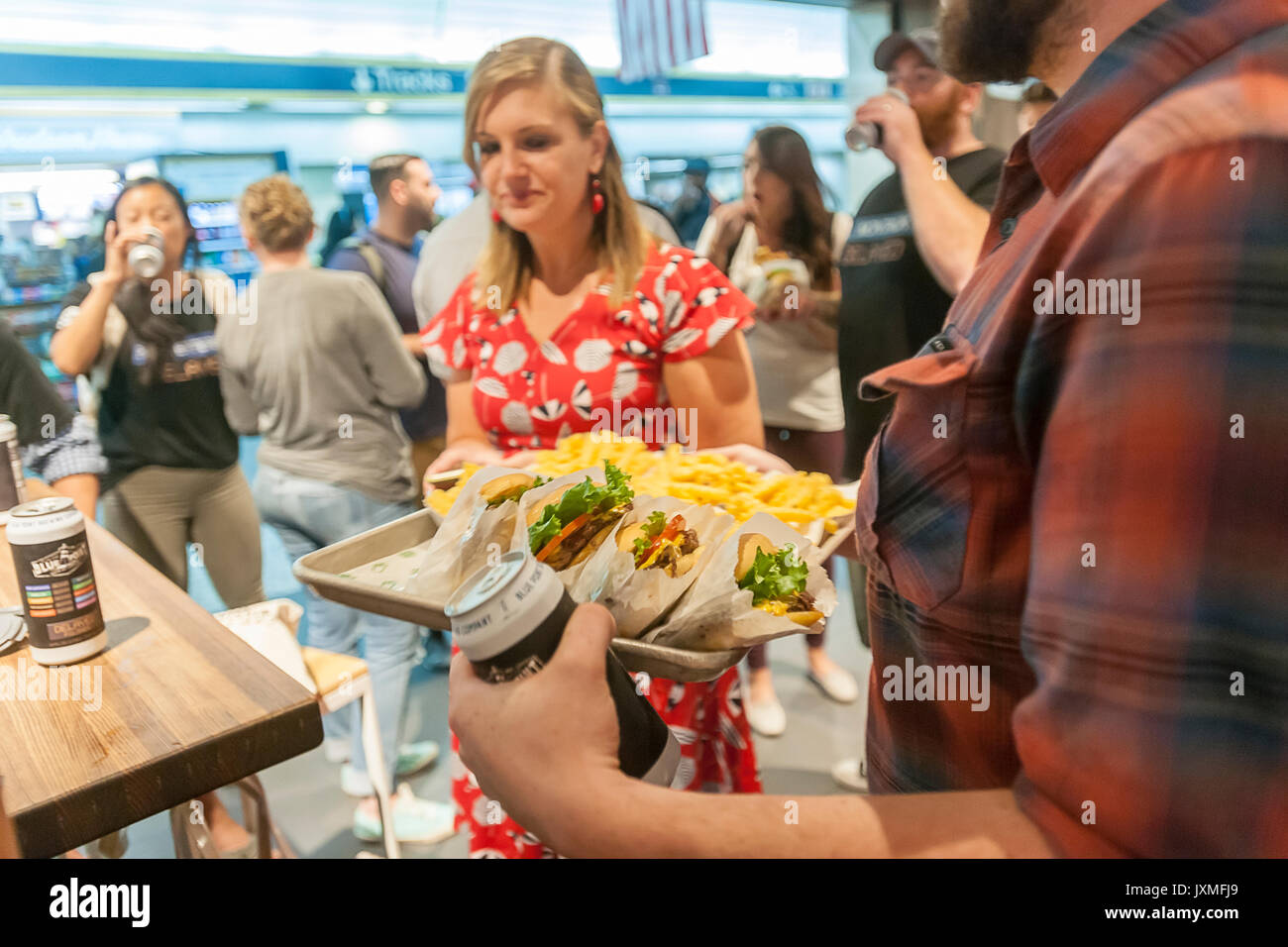 Throngs of hungry burger lovers and thirsty beer drinkers flock to the Shake Shack in Penn Station in New York on Monday, August 14, 2017 for the happy hour debut party of Blue Point Brewery's 'Delayed' beer. Reacting to the 'Summer of Hell' that Long Island Railroad passengers are going through because of maintenance track work Blue Point Brewery created their 'Delayed' pilsner beer with the graphics on the can a riff on the LIRR departure boards. The first 100 customers got a free burger with the purchase of a can of 'Delayed'.  ( © Richard B. Levine) - Stock Image